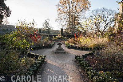 The formal East Garden at the Bishop's Palace garden in Wells, with decorative urn and beds edged with evergreen euonymus planted with a mix of herbaceous perennials and shrubs including red leaved cotinus