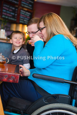 Young mother in a wheelchair with her family in a cafe