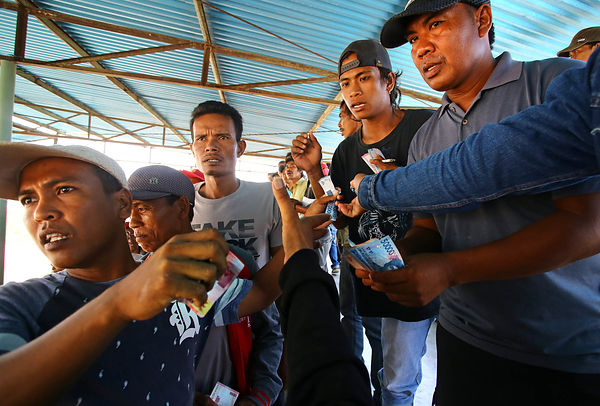 The gamblers in the stands have the eyes fixed on the race. Gambling  is normally prohibited by the indonesian law inspired by Islam but during the races the money flows freely