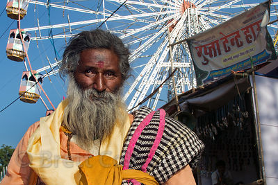 Sadhu in front of a ferris wheel at the Pushkar Camel Fair, Pushkar, Rajasthan, India
