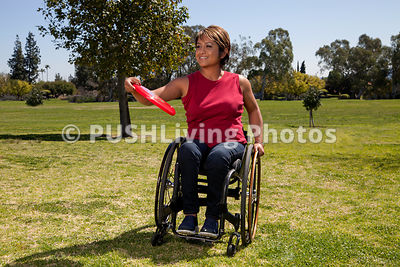 Woman in a wheelchair throwing a frisbee in a park
