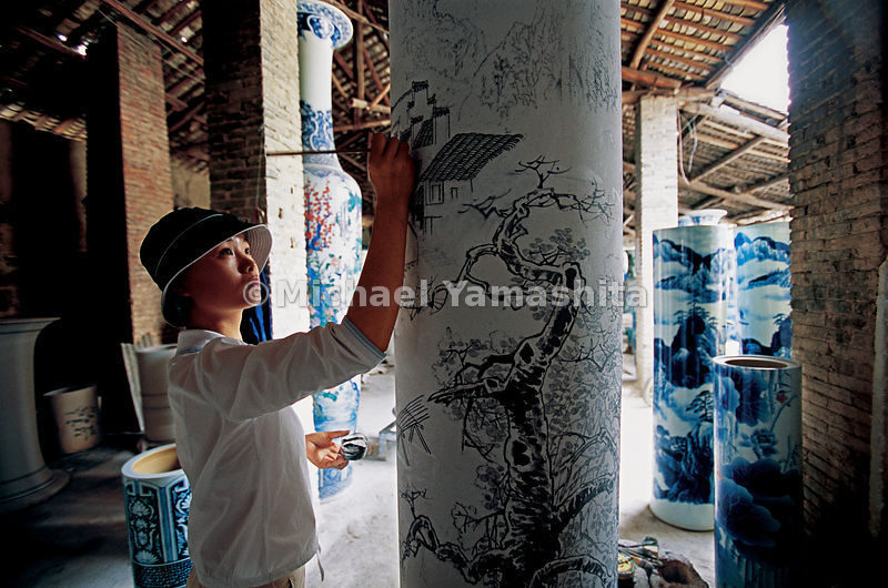The porcelain glaze is applied by hand, the final step before firing in the kilns.