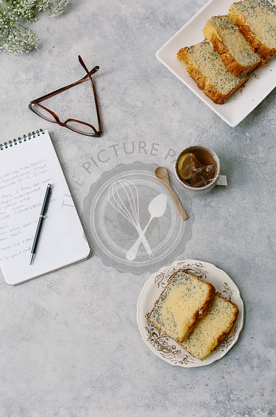 A few slices of pound cake are styled alongside with a notepad and a pair of glasses, photographed from the top view.