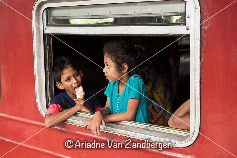 Children looking out of the window of train carriage, Kandy Railway Station, Kande, Sri Lanka