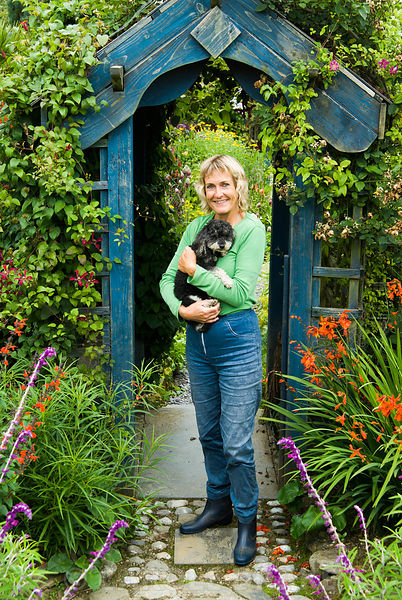 Tina Primmer with her miniature poodle. Poppy Cottage Garden, Roseland Peninsula, Cornwall, UK