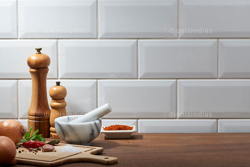 Marble pestle and pepper grinders on wooden background and spices