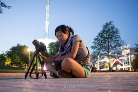 A girl sitting on the ground and taking photographs at an amusement park near London Eye.