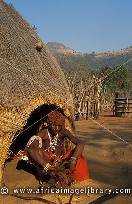 Sangoma 'throwing the bones' in front of his beehive hut, Mantenga village, Swaziland