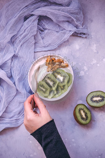 Woman eating yoghurt in a bowl topped with fresh kiwi and walnuts