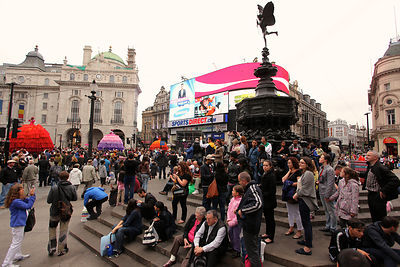 Crowds in Piccadilly Circus with Les Poupées Géantes Ladies in the Background