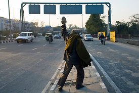 India - Delhi - A homeless mentally ill man picks up a rock to throw at passing traffic