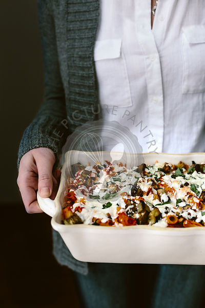 Baked Ziti with Eggplant and Basil in a casserole dish, held by a woman