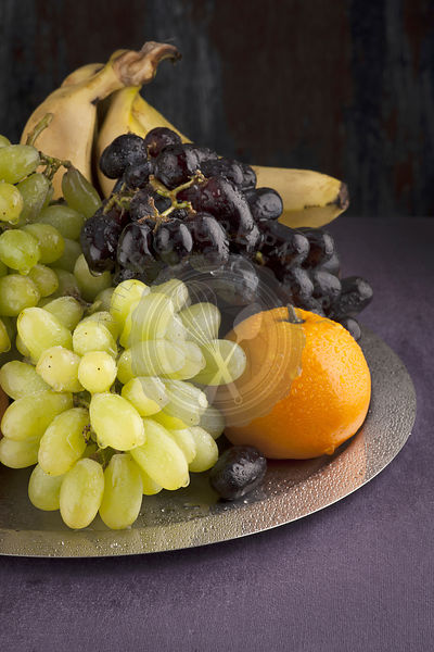 grape oranges and banans on a metal tray