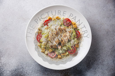 Caesar salad with chicken breast on gray background