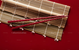 Bambo mat for Sushi with hashis on red background