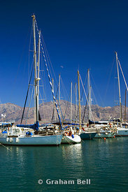 yachts moored in aghios nikolaos marina with the dhikti mountains in the distance, crete, Greece.