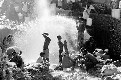 Haitians washing in a water pipe