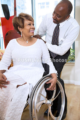Woman using a wheelchair celebrating in the office with her co workers