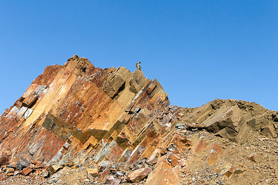 A langur monkey sits on a rocky mountain summit near a rock mine, Kharekhari village, Rajasthan, India