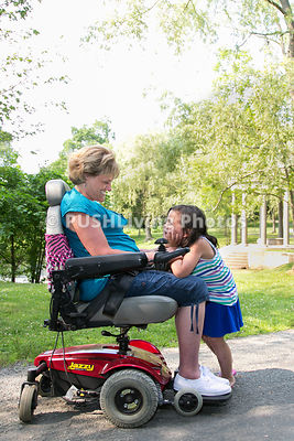 Grandmother using a power wheelchair in a park with her granddaughter