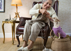 Older Woman in Chair Knitting Next to Small Dog in Basket