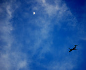 Jet airplane in deep blue sky with moon at top of frame
