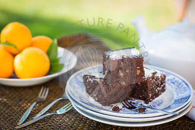 chocolate, orange and walnut brownie on tray with teapot and oranges.