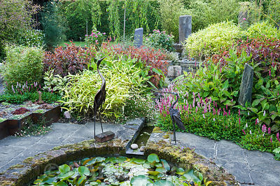 The Carpet Garden features standing stones and a rill that empties into a circular pond beside which two metal birds stand guard. Planting includes strong coloured foliage of persicarias and bamboos. Dipley Mill, Hartley Wintney, Hants, UK