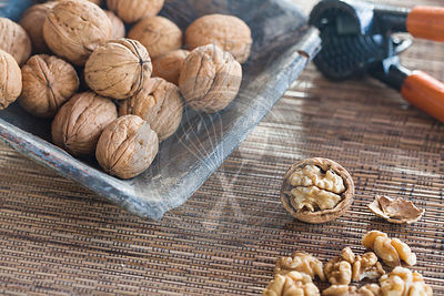 walnuts in shells nestling in a blue square ceramic dish, on woven mat, with nut crackers