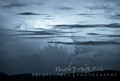 Blue thunderclouds (cumulonimbus) with lower horizontal alto stratus clouds above silhouetted hills.