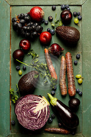 Assortment raw organic of purple ingredients: eggplants, onions, berries, carrots, grapes, cabbage, avocado, plums over rustic background. Top view, gluten free, allergy-friendly, clean eating or raw diet.