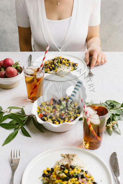 A woman is photographed at a tablesetting with tilapia and black bean salsa in her plate.