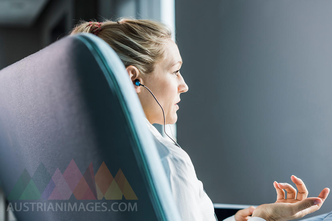 Woman sitting on couch with earphones