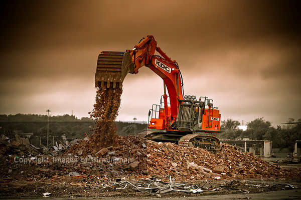 A digger working on the demolition of industrial an site.