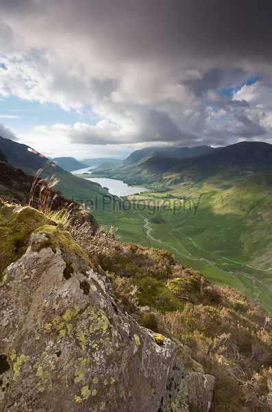 A cloudy sunset over Lake Buttermere from the summit of Haystacks in the Lake District.