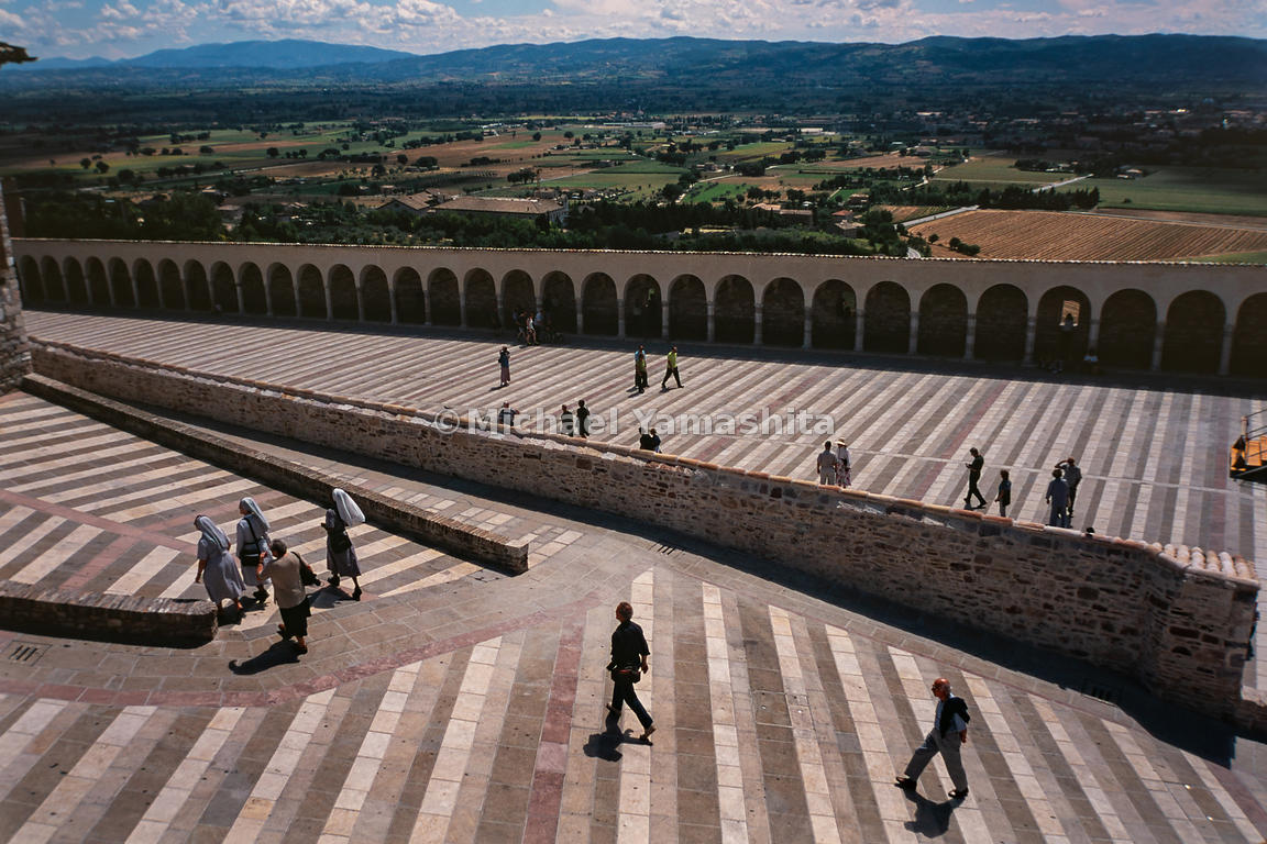 Visitors of the town Assisi roam about a massive rooftop. Assisi, Italy, April, 2001.