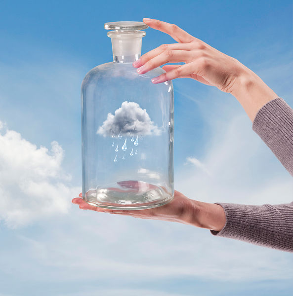 Woman's hands hold glass jar with lid containing rain cloud