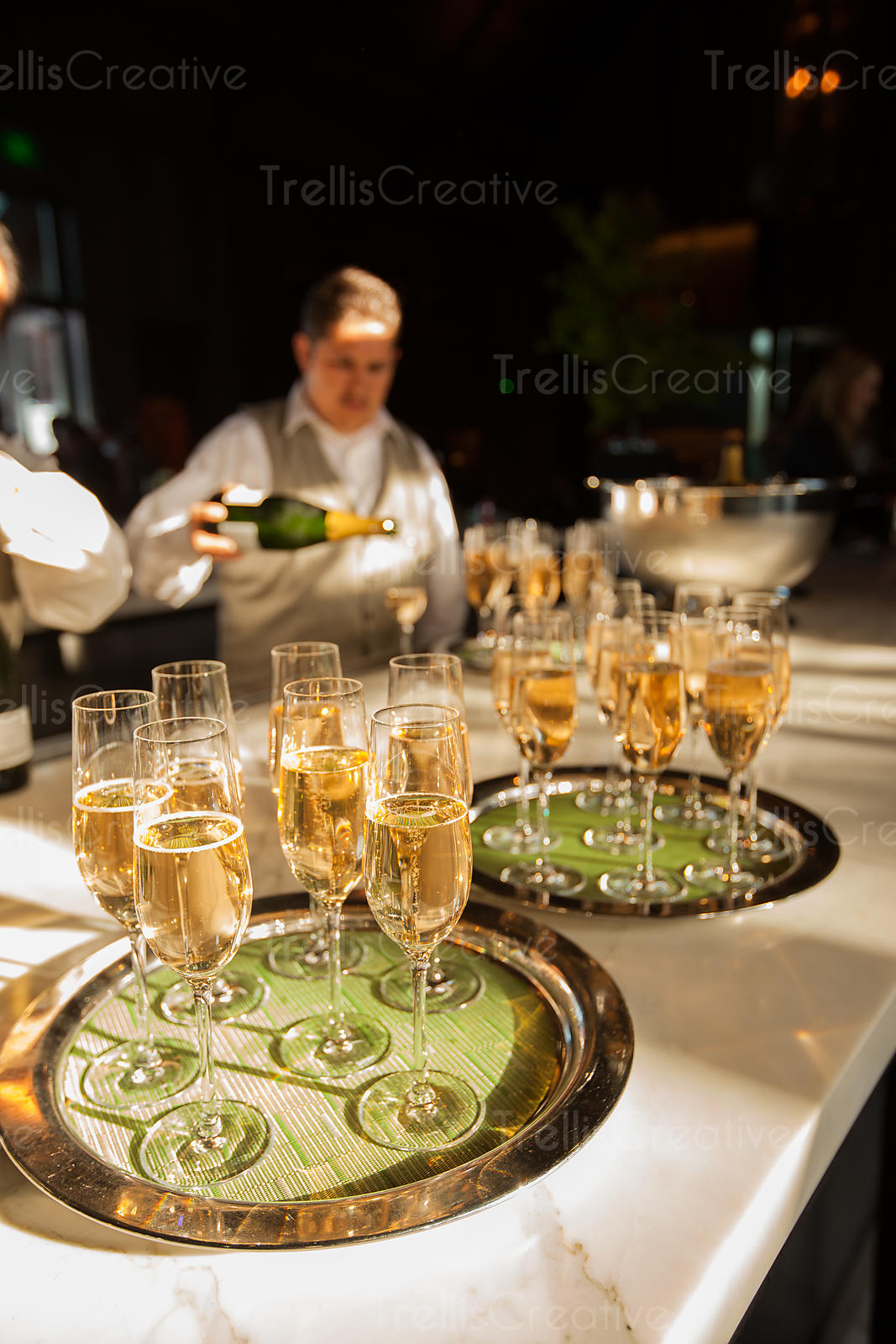 A server fills flutes of champagne and sparkling wine for an elegant party