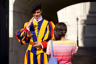 Member of the Swiss Guard saluting a Tourist in Vatican City