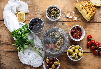 Olive tapenade in the making in a marble mortar is photographed from top view. Three types of olives, capers, sun-dried tomatoes herbs, corn bread slices accompany it.