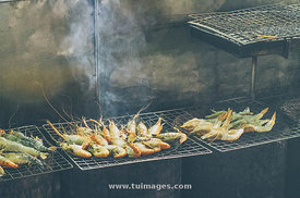 grilling prawns on metal grid.