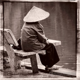 Woman with Hat Sitting on Bench by Lake