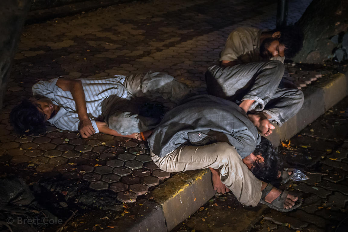 Men who have either passed out drunk or are sleeping after a hard day's work at a construction site, or borh. On the street in Bandra East, Mumbai, India.