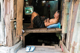 A local watching television inside his house in Bangkok.