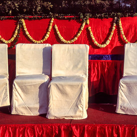A stage set for a wedding with chairs and garlands
