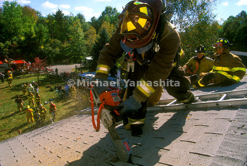 fireman cutting the roof of a house.
