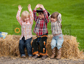 Three young children in western clothes sitting on a bale of straw