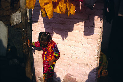 India - New Delhi - A chld plays outside her house in the lanes of Shadipur Depot