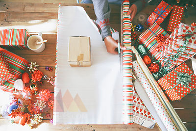 Woman cutting wrapping paper for Christmas gifts