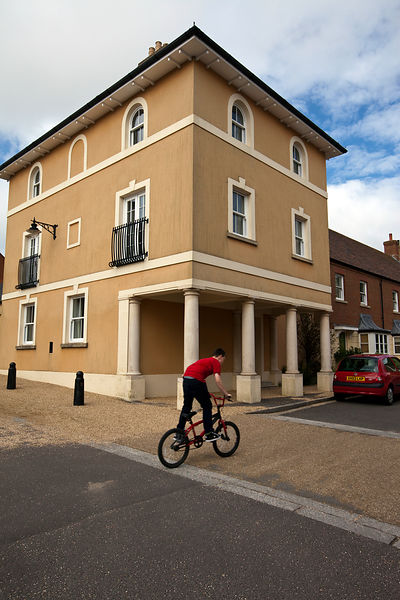 UK - Dorset - A boy rides his bicycle past a  traditionally styled building in Poundbury.